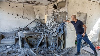 A man stands inside a house that was hit by a rocket fired from the Gaza Strip in the southern Israeli city of Ashkelon, on November 13, 2018. Photo by Nati Shohat/Flash90