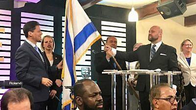 Pastors Josimar Salum and Robert Stearns holding the Israeli flag at a recent CAMERA event.