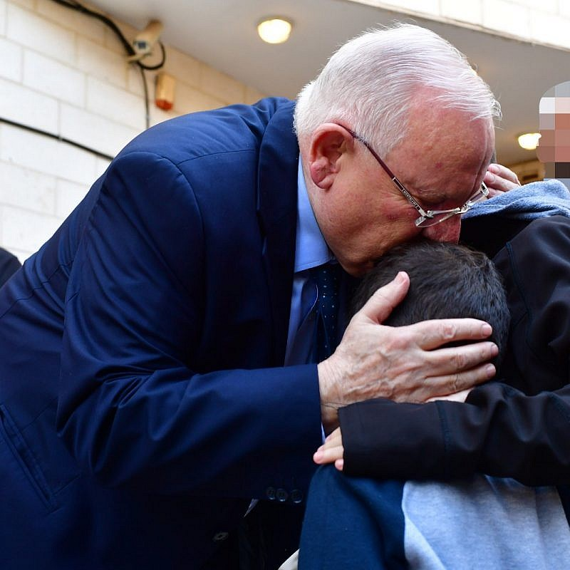 "Israeli President Reuven Rivlin hugging the children of Lt. Col. M at their father's funeral, telling the children ""your dad was a hero, the greatest hero."" Credit: Kobi Gideon/GPO."