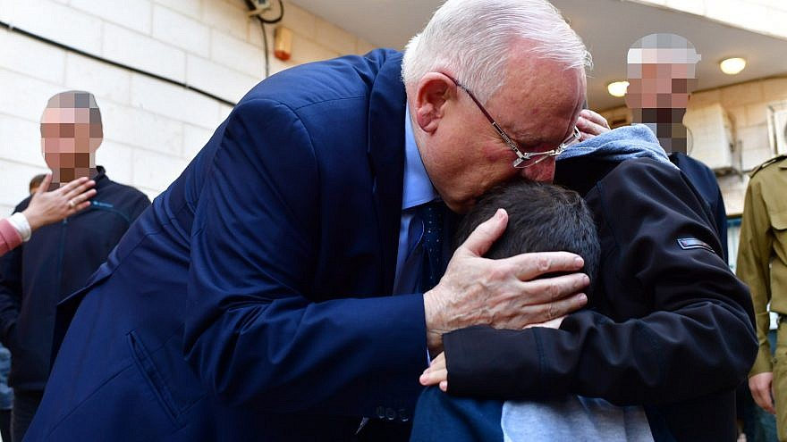 "Israeli President Reuven Rivlin hugging the children of Lt. Col. M. at their father's funeral, telling the children ""your dad was a hero, the greatest hero."" Credit: Kobi Gideon/GPO."