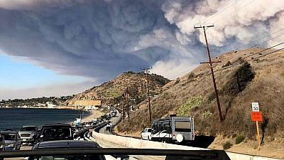 The smoke plume from the fast-moving Woolsey Fire encroaching on Malibu, Calif., on Nov. 9, 2018, as residents evacuate along the Pacific Coast Highway. Credit: Wikimedia Commons.