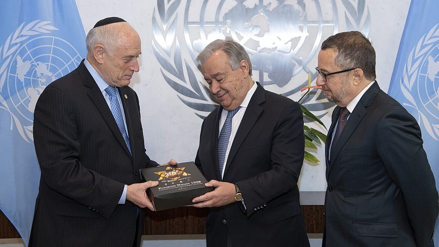 "Malcolm Hoenlein (left), CEO and vice chair of the Conference of Presidents, presents a two-volume set of books titled ""Pogrom Night 1938"" to U.N. Secretary General António Guterres. Credit: Conference of Presidents of Major American Jewish Organizations."