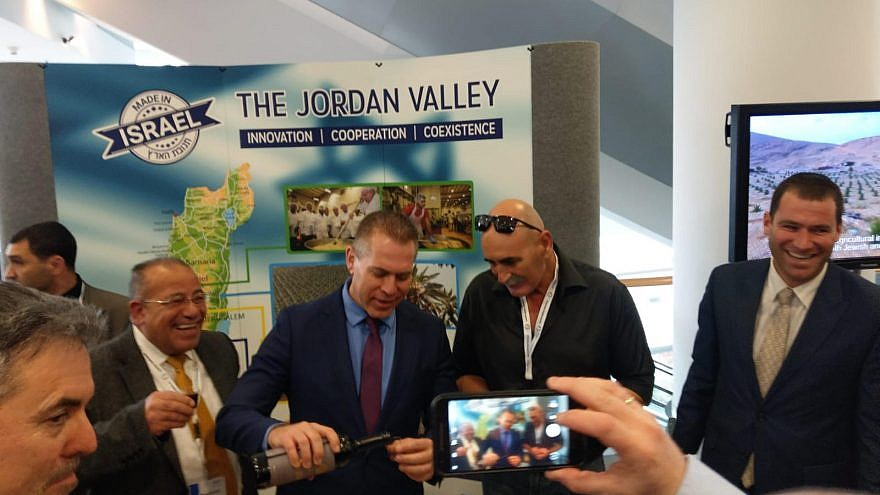 Minister of Strategic Affairs pours wine from Judea and Samaria at Israel Kongress in Frankfurt, together with the head of the Jordan Valley Regional Council David Elhayani and Palestinian human-rights activist Baseem Eid. Credit: Jordan Valley Regional Council.