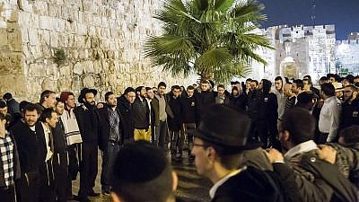 """A group of students and rabbis sing """"Acheinu"""" at the site outside the Jaffa Gate in Jerusalem where Rabbi Reuven Biermacher, 45, a husband and father of seven, was stabbed and killed by Palestinian terrorists on Dec. 23, 2015. Credit: Aish HaTorah."""