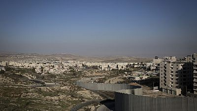 The separation wall runs along the Palestinian refugee camp, Shuafat, separating it from the Jewish town of Pisgat Ze'ev, near Jerusalem, on Jan. 29, 2014. Photo by Hadas Parush/Flash 90.