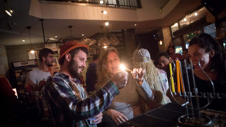 Young Israelis light candles for the Jewish holiday of Hanukkah at a bar in Tel Aviv on Dec. 8, 2015.  Photo by Miriam Alster/Flash90.
