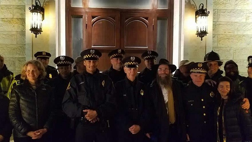 Eleven Pittsburgh police officers, who were among the first responders to the Oct. 27 mass shooting that claimed 11 lives in a Squirrel Hill synagogue, helped light the menorah at Chabad of Roslyn on Long Island, N.Y. Credit: Chabad.org/News.