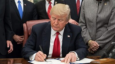 U.S. President Donald Trump signing legislation in the Oval Office, January 2018.  Source: White House.