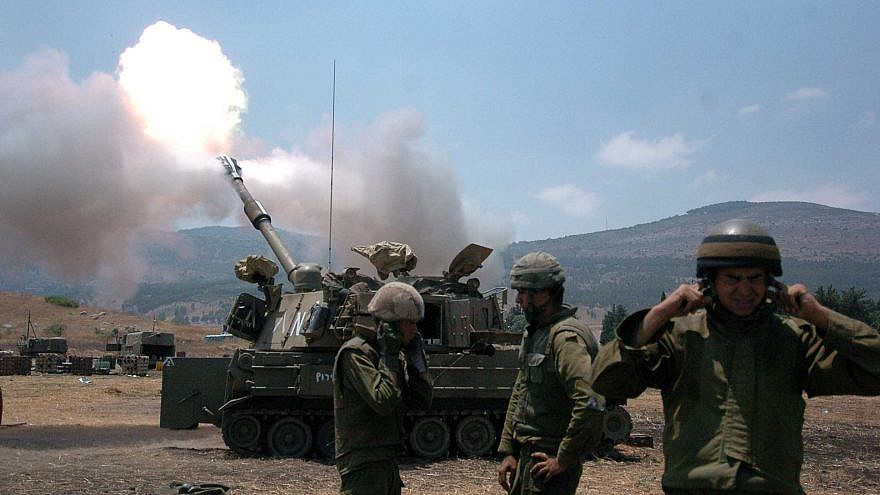 Israeli soldiers cover their ears as a tank fires into Lebanon from Kiryat Shemona on July 20, 2006, during the Second Lebanon War. Credit: Guy Assayag /Flash90.