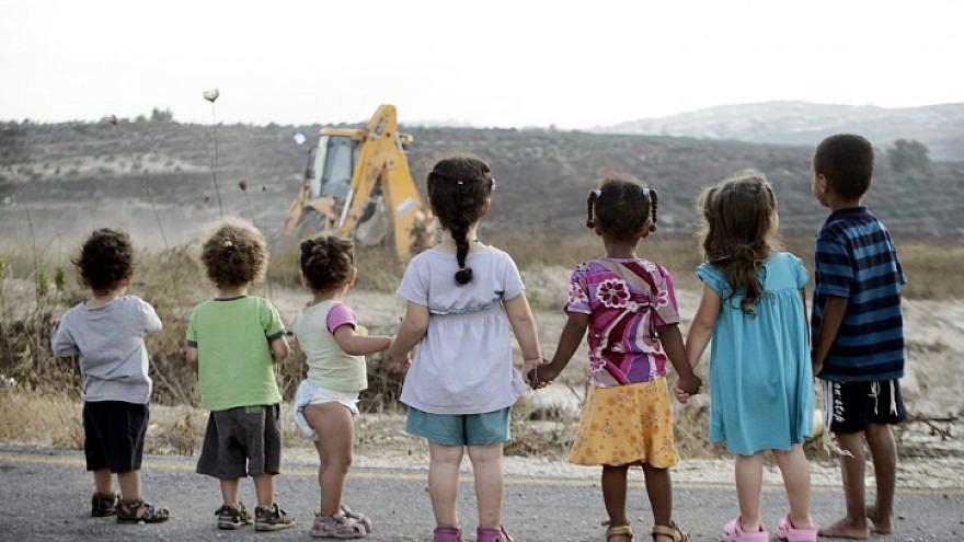 Israeli children look on at building in Kdumim in Judea. Photo by Uri Lenz/Flash90.