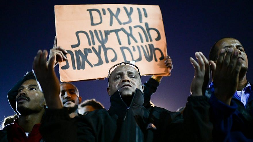 """Israelis, many of them Ethiopian, protest against police violence in Tel Aviv on Jan. 30, 2019. This sign in Hebrew reads: """"Leaving the apathy, changing the reality."""" Photo by Tomer Neuberg/Flash90."""