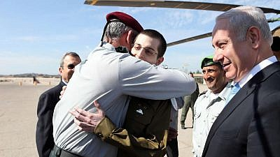 Israel Defense Forces' Chief of Staff Lt. Gen. Benny Gantz embraces IDF soldier Gilad Shalit upon his return from captivity, alongside Israeli Prime Minister Benjamin Netanyahu, on Oct. 18, 2011. Credit: IDF Photo via Wikimedia Commons.