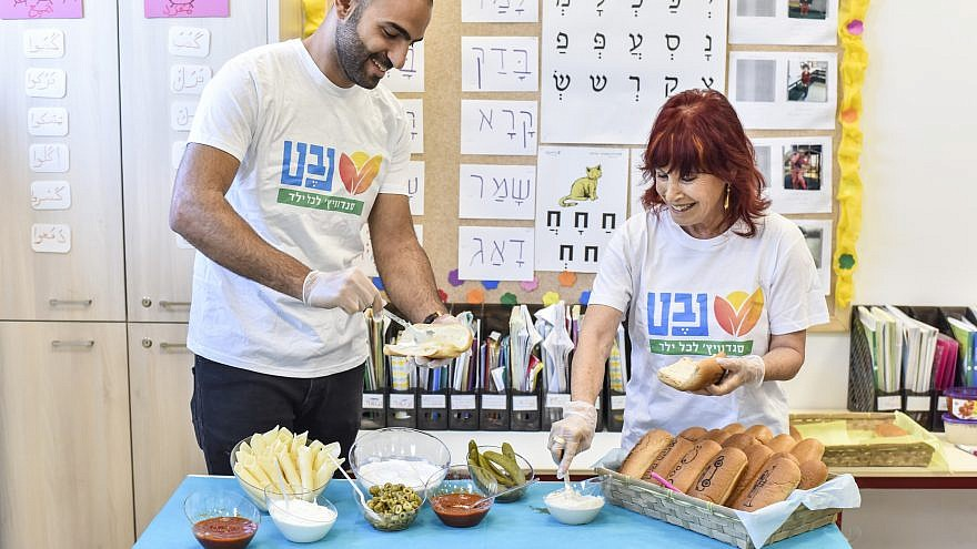 Staff with Nevet, an organization based in Ra'anana, Israel, prepare breakfast sandwiches for children in need throughout the country. January 2019. Credit: Omri Shapira.
