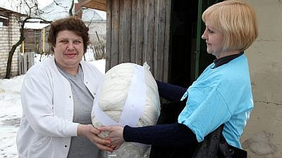 Warm bedding is delivered to Svetlana M. in Babruysk, Belarus, from a representative of the American Jewish Joint Distribution Committee's Hesed Social Welfare Center. Credit: JDC.