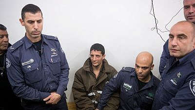 Police escort a Palestinian charged with the murder of 19-year-old Ori Ansbacher, at the Jerusalem Magistrate's court, on Feb. 11, 2019. The suspect was captured hiding in Ramallah after Israeli forces investigated the scene where the young woman was found dead last week in Ein Yael, in the outskirts of Jerusalem. Photo Yonatan Sindel/Flash90.