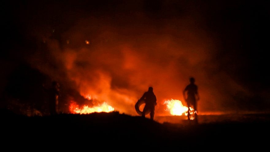 Palestinian protesters burn tires during a night protest near the border with Israel, east of Rafah in the southern Gaza Strip, on Feb. 14, 2019. Photo by Abed Rahim Khatib/Flash90.