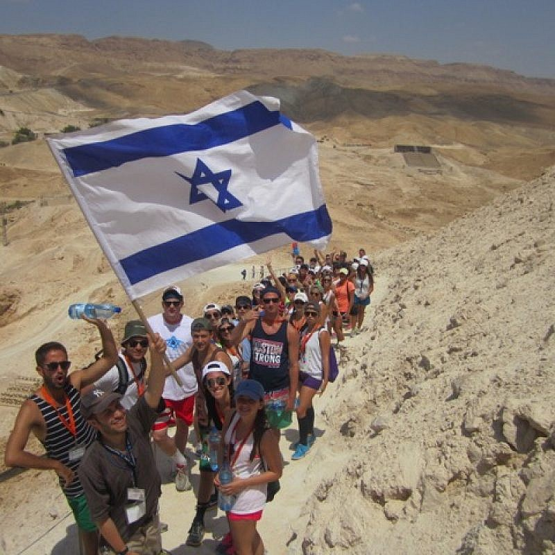 Birthright participants hike up Israel's Msasda while waving an Israeli flag. Credit: Birthright Israel.