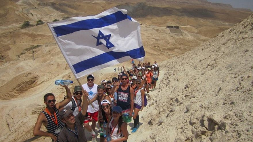Birthright Israel participants hike up Masada, Israeli flag in hand. Credit: Courtesy.