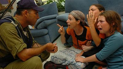 An Israeli soldier evacuate Jewish settlers women from their house in the Jewish settlement of Newe Dekalim in the Gaza Strip, 2005. Photo by Flash90.