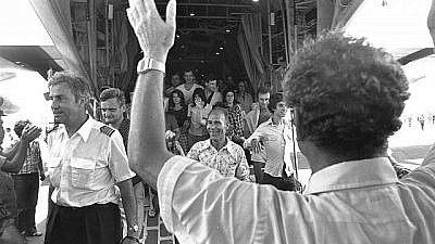 Israeli Foreign Minister Yigal Allon (back to camera) welcoming the rescued Air France passengers and crew, including pilot Michel Bacos (left), coming off an Israel Air Force Hercules plane at Ben-Gurion International Airport, July 1976. Credit: Moshe Milner/Israel Government Press Office.