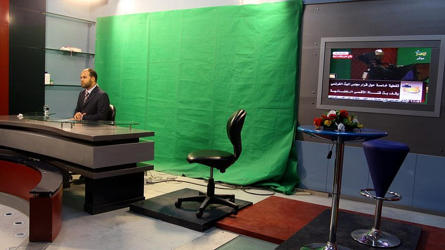 A Palestinian broadcaster presents a newscast at the Hamas Al-Aqsa TV station in Gaza City on June 17, 2010. Credit: Abed Rahim Khatib/Flash90.