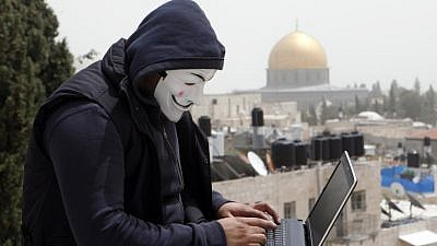 A Palestinian youth wearing masks used by computer hackers who attacked a number of Israeli websites recently, seen backdropped by the Temple Mount in Jerusalem's Old City, April 8, 2013. Photo by Sliman Khader/Flash90.