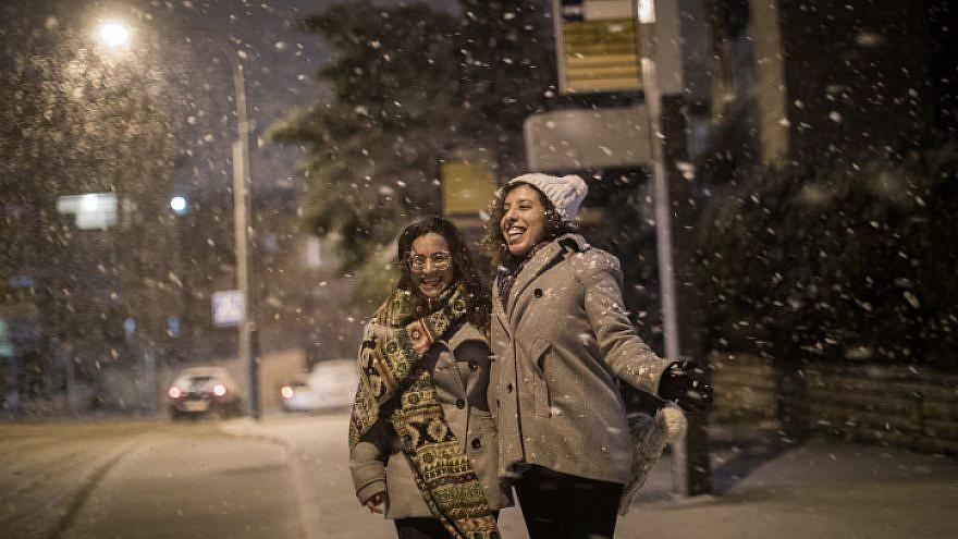 Israeli women enjoy the snow as it falls in the Old Katamon neighborhood of Jerusalem on Jan. 16, 2019. Photo by Hadas Parush/Flash90.