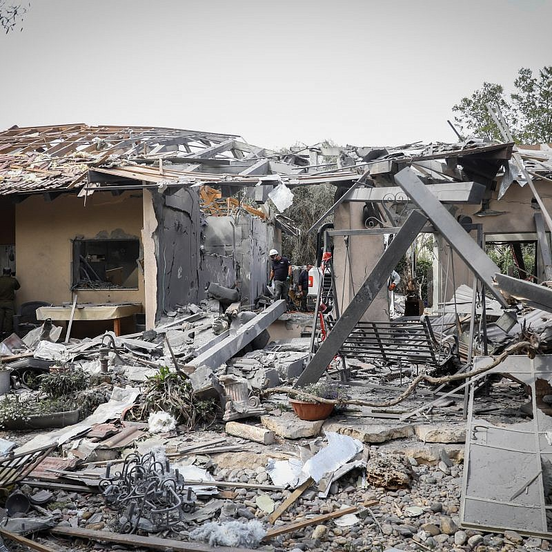 Israeli security forces inspect the scene of a house that was hit by a rocket fired from the Gaza Strip in Moshav Mishmeret, central Israel, on March 25, 2019. Credit: Noam Revkin Fenton/Flash90