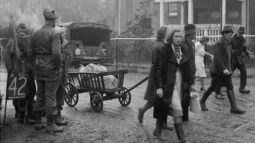 Scottish troops watch as German refugees stream back through the village of Bedburg near Kleve, Feb. 19, 1945. Credit: Imperial War Museum, London, part of the War Office Second World War Official Collection.