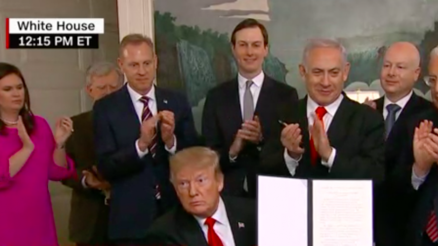 U.S. President Donald Trump holds up a signed declaration of U.S. recognition of Israeli sovereignty over the Golan Heights on March 25, 2019 at the White House. Credit: CNN Screenshot.