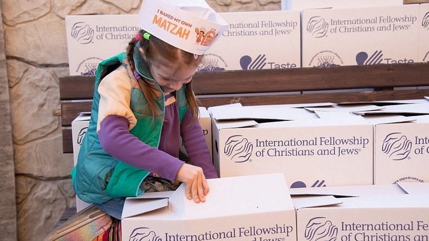 A young girl helps pack boxes containing food and other items to be sent to Jews in need. Credit: Federation of the Jewish Communities of the Commonwealth of Independent States.