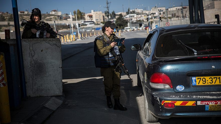 An Israeli soldier from the Erez Battalion checks IDs and Palestinian vehicles at the checkpoint to the Shuafat Refugee Camp in eastern Jerusalem on Dec. 22, 2015. Credit: Hadas Parush/Flash90.