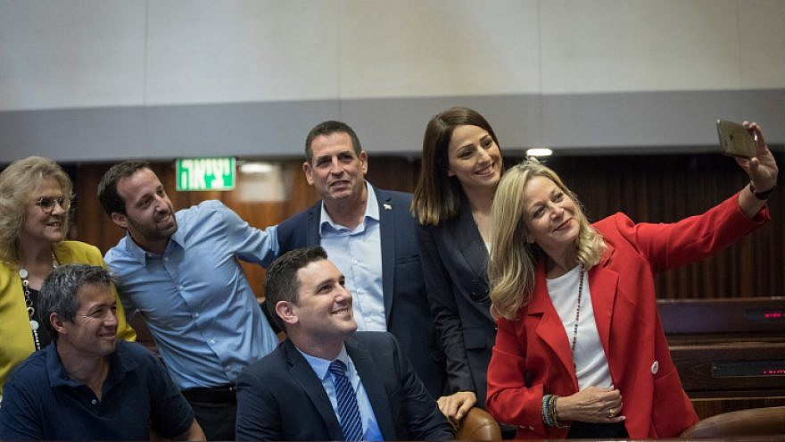 New Knesset members Yoaz Hendel, Yorai Lahav-Hertzano, Miki Haimovich, Yehiel Tropper and Zvi Hauser are part of a selfie taken at the Knesset Plenary Hall ahead of the opening session of the new government, on April 29, 2019. Photo: Noam Revkin Fenton/Flash90.