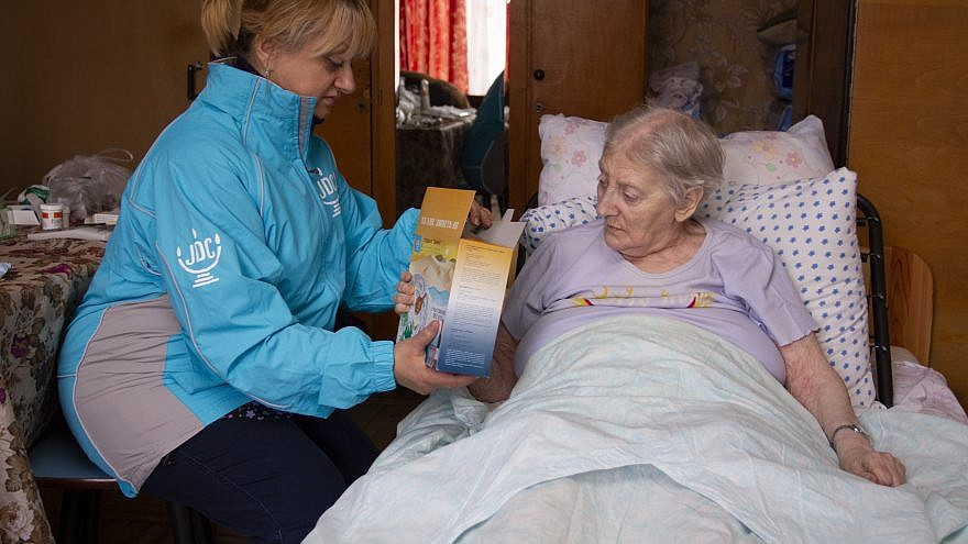 Continuing JDC's long-held tradition of matzah delivery for Passover, a volunteer provides matzah to elderly client in Odessa, Ukraine. Credit: Courtesy.