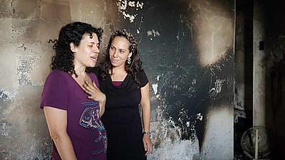 Dari Carlebach (left), daughter of the late Rabbi Shlomo Carlebach, and Yael Eckstein, daughter of the late Rabbi Yechiel Eckstein, examine damage by fire to nearly 50 homes in moshav Mevo Modi'im, May 27, 2019. Credit: IFCJ.