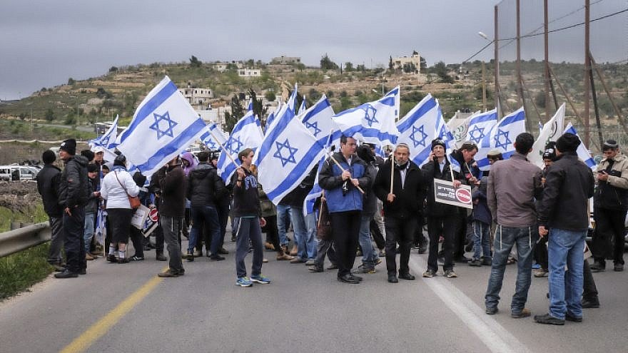 """Hundreds march with Israeli flags and signs reading """"bringing back deterrence"""" from the Jewish settlement of Karmei Tzur to the Gush Etzion Junction in the settlement bloc in the West Bank, on March 15, 2016. Photo by Gershon Elinson/Flash90."""