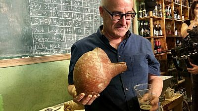Professor Aren Maeir, from Bar-Ilan University's Land of Israel studies and archaeology, models an ancient vessel and the new, recreated beer. Credit: Eliana Rudee.