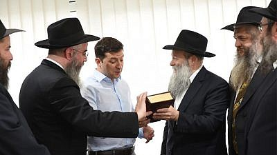 President-elect Volodymyr Zelensky, Ukraine's first-ever Jewish president, held a high-profile meeting with Ukraine's regional chief rabbis on May 6. Here, the comedian-turned-politician is presented with a Chumash in Russian translation by Rabbi Shmuel Kaminezki and Rabbi Avraham Wolff, as other members of the delegation look on. Credit: Chabad.org/News.