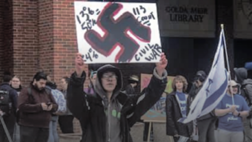 Kristian Gresham, 26, a student at the University of Wisconsin-Milwaukee protested an Israel Independence Day event with a sign consisting of a swastika and anti-Semitic messages, May 6, 2019. Credit: Change.org.