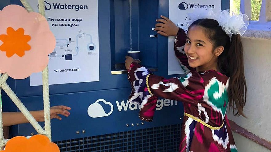 """A girl in Bukhara, Uzbekistan, samples water from an atmospheric water generator known as the """"GEN-350,"""" May 2019. Credit: Watergen."""