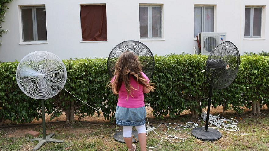 A young girl cools herself on a hot summer day by standing next to fans at the Zitan yishuv, on Aug. 15, 2012. Photo by Nati Shohat/Flash90.