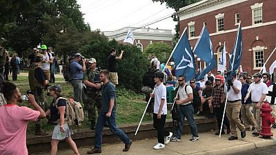 A group of people carrying Identity Europa flags (and one Ohio flag) march in front of clergy as they arrive at Emancipation Park in Charlottesville, Va., in August 2017. Credit: Anthony Crider/Wikimedia Commons.