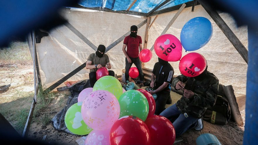 Palestinians prepare balloons that will be attached to flammable material to be launched into Israel from the Gaza Strip, on June 25, 2019. Photo by Hassan Jedi/Flash90.