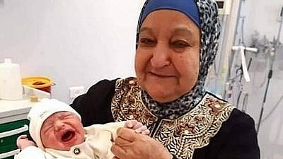 "The text accompanying this image, which was posted to the official Fatah Facebook page on June 15, reads: ""A child from smuggled sperm. The mother of prisoners and martyrs, Um Nasser Abu Hmeid, holds her grandson Yaman in her arms, the son of prisoner Nasr Abu Hmeid, who is serving five life sentences."" (PMW)"
