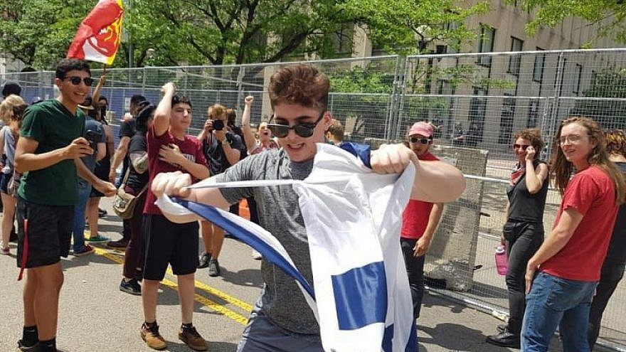 A counter-protester tears an Israeli flag on Third Street in Dayton next to Courthouse Square, the site of the Ku Klux Klan-affiliated Honorable Sacred Knights of Indiana's rally, May 25, 2019. Photo by Corine Fairbanks.