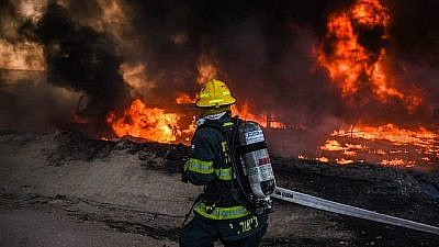 An Israeli firefighter works to extinguish a blaze caused by an incendiary device sent from Gaza into southern Israel on June 27, 2019. Credit: Israel Fire and Rescue Services.