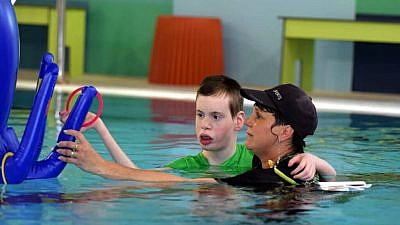 A hydrotherapist works with a resident with severe complex disabilities at the ALEH hydrotherapy pool in Jerusalem. Credit: ALEH.