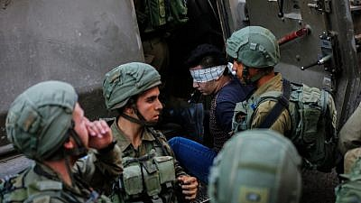 Illustrative: Israeli soldiers arrest a Palestinian man during raids in Hebron, on September 20, 2017. Photo by Wisam Hashlamoun/Flash90.