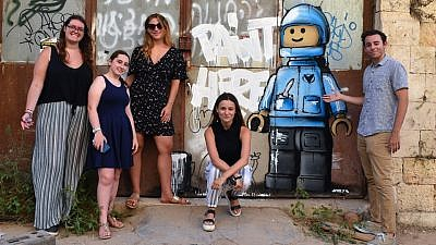 TIIF interns pose next to a painting by British artist Ame72. Credit: Courtesy.