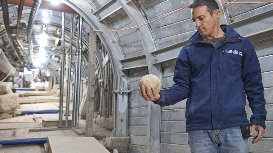 Nachshon Zenton, one of the directors of the Pilgrimage Road excavation in Jerusalem's City of David, holds a catapult projectile apparently  used during the Great Jewish Revolt. Credit: Shai Halawi, Israel Antiquities Authority.